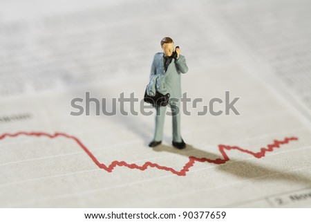 Analysing Business Statistics, a miniature model businessman stands over a red line graph talking on his mobile phone.