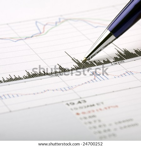 Analysis of a printed stock price chart, pointing with pen at chart feature. - stock photo