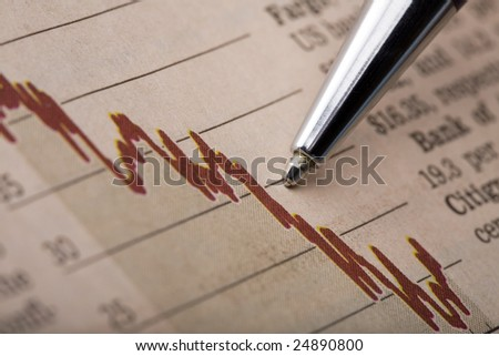 Analysis of a stock chart printed in a financial newspaper. Pen tip pointing at a declining red line graph.