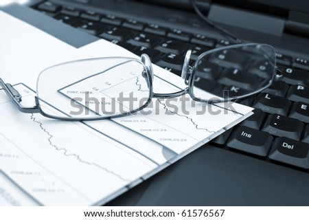 Analysis of business reports on a laptop.