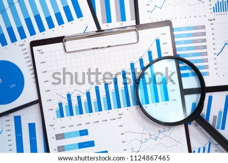 Analyzing and gathering statistical data. Growth charts. Many business reports and magnifying glass.  #1124867465