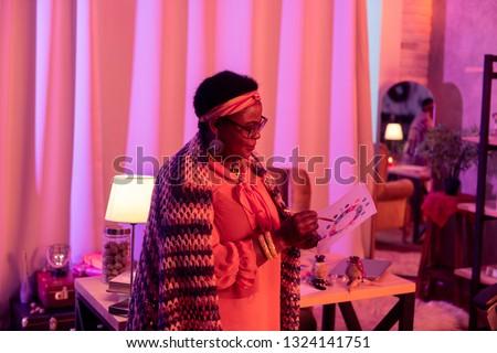 Analyzing birth chart. African american plump fortune-teller wearing eyeglasses checking birth chart