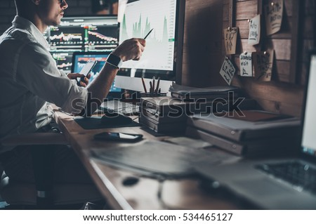 Analyzing data. Close-up of young businessman looking at monitor while sitting at the desk in creative office