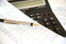 Analyzing finance report with calculator and pen
