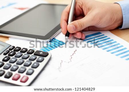 Analyzing financial data on calculator - stock photo