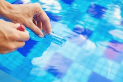 Analyzing of a water from swimming pool, taking water sample to a flask