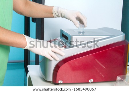 Anatomic pathology tests, Histopathology And Cytopathology. Histology test lab in hospital. Hands in gloves load slide glasses with patient biopsy sections in high throughput automatic staining device
