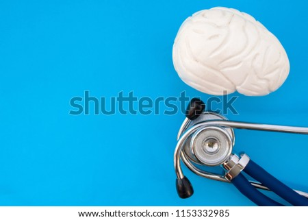 Anatomic study model of brain and stethoscope on blue background occupy half of photo, in second half - empty space for titles. Medical concept photo for use in neurology, psychiatry, mental health #1153332985