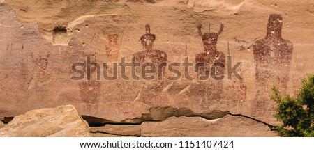 """Ancestral Puebloan or Anasazi petroglyphs of strange anthropomorph figures, often referred to as """"ancient aliens"""" on the wall of Sego Canyon in Thompson Springs, Utah."""