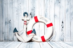 Anchor and life buoy on a background of white shabby wall boards.
