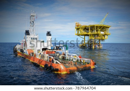 Anchor handling tug deploying anchor for diving support barge with wellhead platform background. #787964704