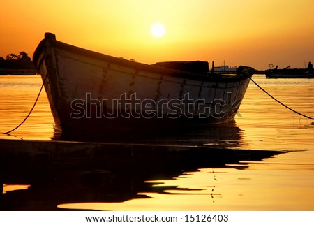 Anchored boat at sunrise in Ria Formosa (Portugal) - stock photo