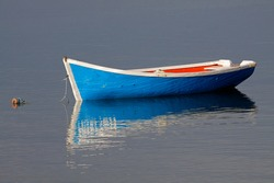 Anchored wooden fishing boat with reflection in water