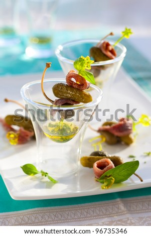 Anchovies with capers and cornichons on cocktail sticks