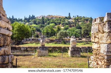 Ancient Agora in summer, Athens, Greece. It is famous tourist attraction of Athens. Panorama of Agora with classical Greek ruins of historical Athens. Urban landscape of old Athens city center.