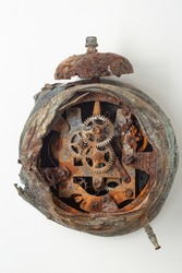 Ancient alarm clock with only one leg, worn by time, historical, without front side, broken clock. Clockwork exposed with rusted parts, alarm clock is in poor condition. Isolated on light background.