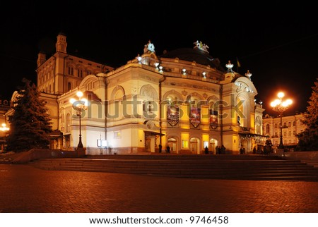 Ancient alight building of Kiev opera against the dark night and block pavement square in the foreground