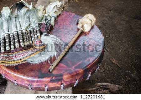Ancient amerindian tambourine, drum drumstick replica and a feather headdress