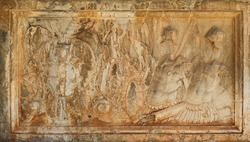 Ancient and rusty relief with the scene of a medieval war with armors, engraved in white stone - background wallpaper