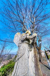 Ancient angel statue, used as christian decoration in an ancient italian cemetery (Oltrepò Pavese, Lombardy, Northern Italy). Wintertime view.
