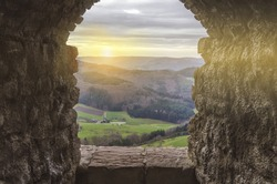 Ancient arch window in the castle at sunset