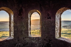 Ancient arch windows in a castle with scenic hills at sunset