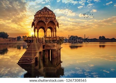 Ancient architecture ruins at Gadi Sagar (Gadisar) lake Jaipur Rajasthan at sunrise with vibrant moody sky.  #1267308565