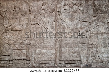 Ancient assyrian clay relief depicting a row of warriors with weapons and text written in cuneiform writing - stock photo