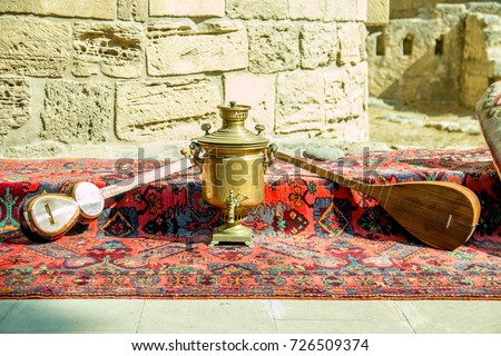 Ancient azerbaijani musical instruments tar and saz mock up with old vintage azeri tea pot for boiling water.