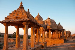 Ancient Bada Bagh cenotaphs in desert, also known as Jaisalmer Chhatris made of yellow sandstone at sunset in Jaisalmer, Rajasthan state, India