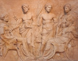 Ancient bas-relief on funerary stele from Kerameikos in Athens, Greece depicting man and woman sit faced each other and tree more figures, two men and a women stand in background.