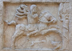 Ancient bas-relief on funerary stele from Kerameikos in Athens, Greece depicting rider in hunting scene. Gravestone of Attica-type.