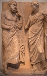 Ancient bas-relief on funerary stele from Kerameikos in Athens, Greece depicting standing man and woman.