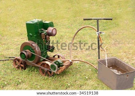Ancient belt-driven motor pump filling a tank with water - the drive wheel is being driven around