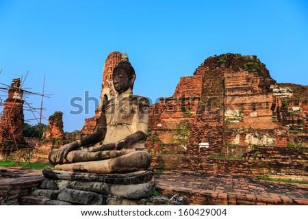 ancient big Buddha statue in front of damaged brick pagoda on blue sky background, Ayutthaya Thailand