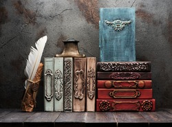 Ancient books, manuscripts and an antique inkwell on a shelf