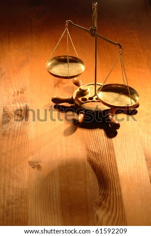 Ancient brass weight scale standing on nice wooden background