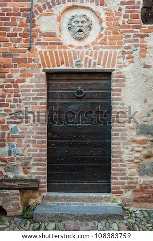 Ancient brick building with wooden door and stone carving