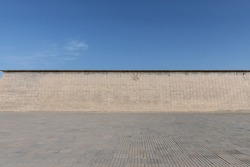 ancient brick wall with blue brick ground against a sunny sky, nice background
