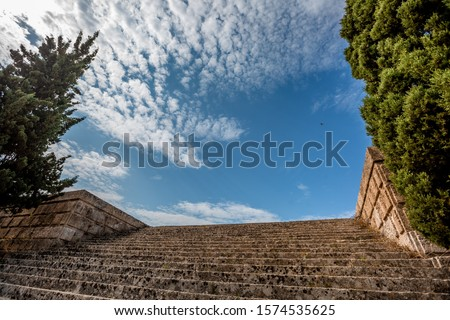 Ancient broad stairway of Acropolis Rhodes bottom view with green bushy trees on left and right sides, blue skies with light white clouds and bird skyline
