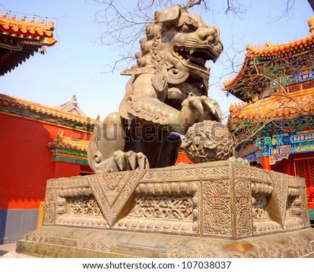Ancient bronze lion and red chinese paviliones in famous Lama Temple (Beijing, China)