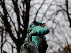 Ancient bronze statue of the streets of Vienna with three sparrows on top.