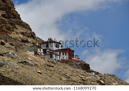 Ancient Buddhist monastery on the mountainside opposite the southern face of mount Kailash (Kailash) in cloudy weather #1168099270