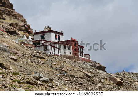 Ancient Buddhist monastery on the mountainside opposite the southern face of mount Kailash (Kailash) in cloudy weather #1168099537
