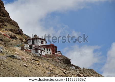 Ancient Buddhist monastery on the mountainside opposite the southern face of mount Kailash (Kailash) in cloudy weather #1168356367