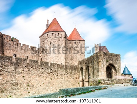 Ancient castle Carcassonne. Ancient fortress with towers and blue sky with clouds in background. Languedoc, France, Europe.