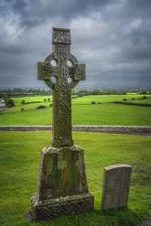 Ancient Celtic cross as gravestone with green fields and dramatic storm sky in background, Cashel, Ireland