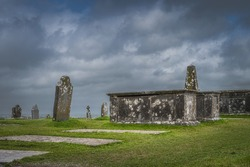 Ancient Celtic cross, gravestone and tombs with dramatic storm sky in background in Rock of Cashel, Ireland