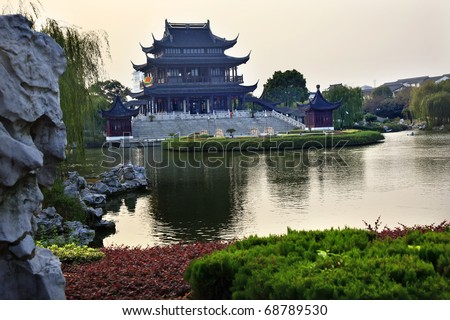 Ancient Chinese Hall of Four Auspicious Merits and Hall of Attractive Scenery Pan Men Scenic Ares  Suzhou, Jiangsu, China Garden Lake Reflection Flag is not a trademark.  It says tea in Chinese. - stock photo