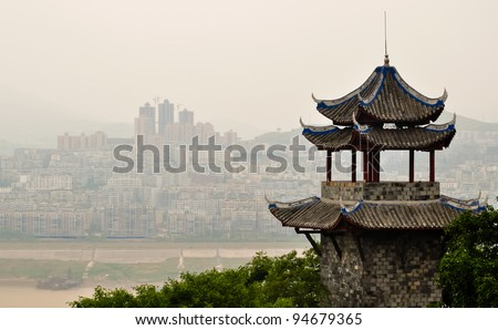 ancient chinese pagoda overlooking yangtze river against a modern skyline